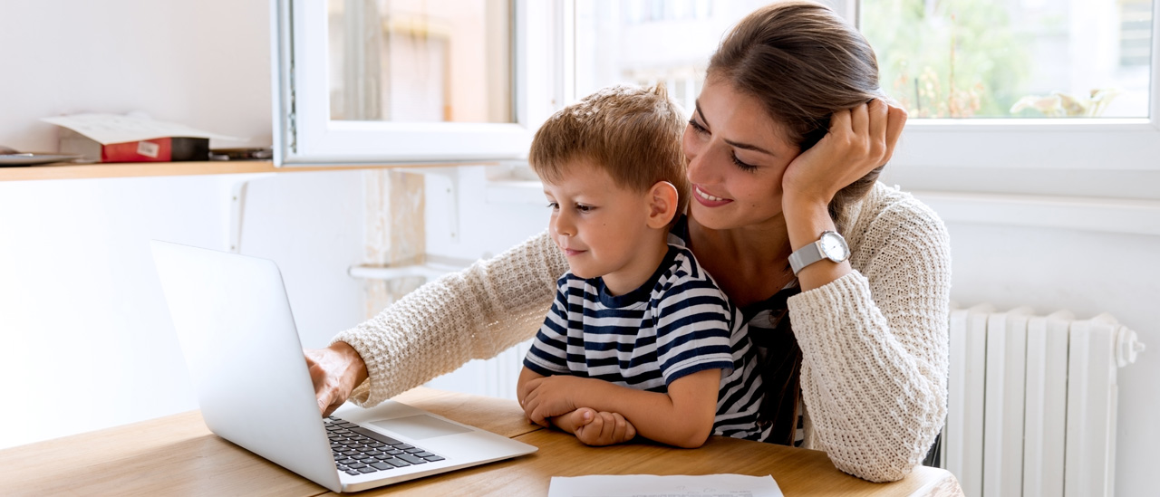 Woman and child viewing a laptop with a smile